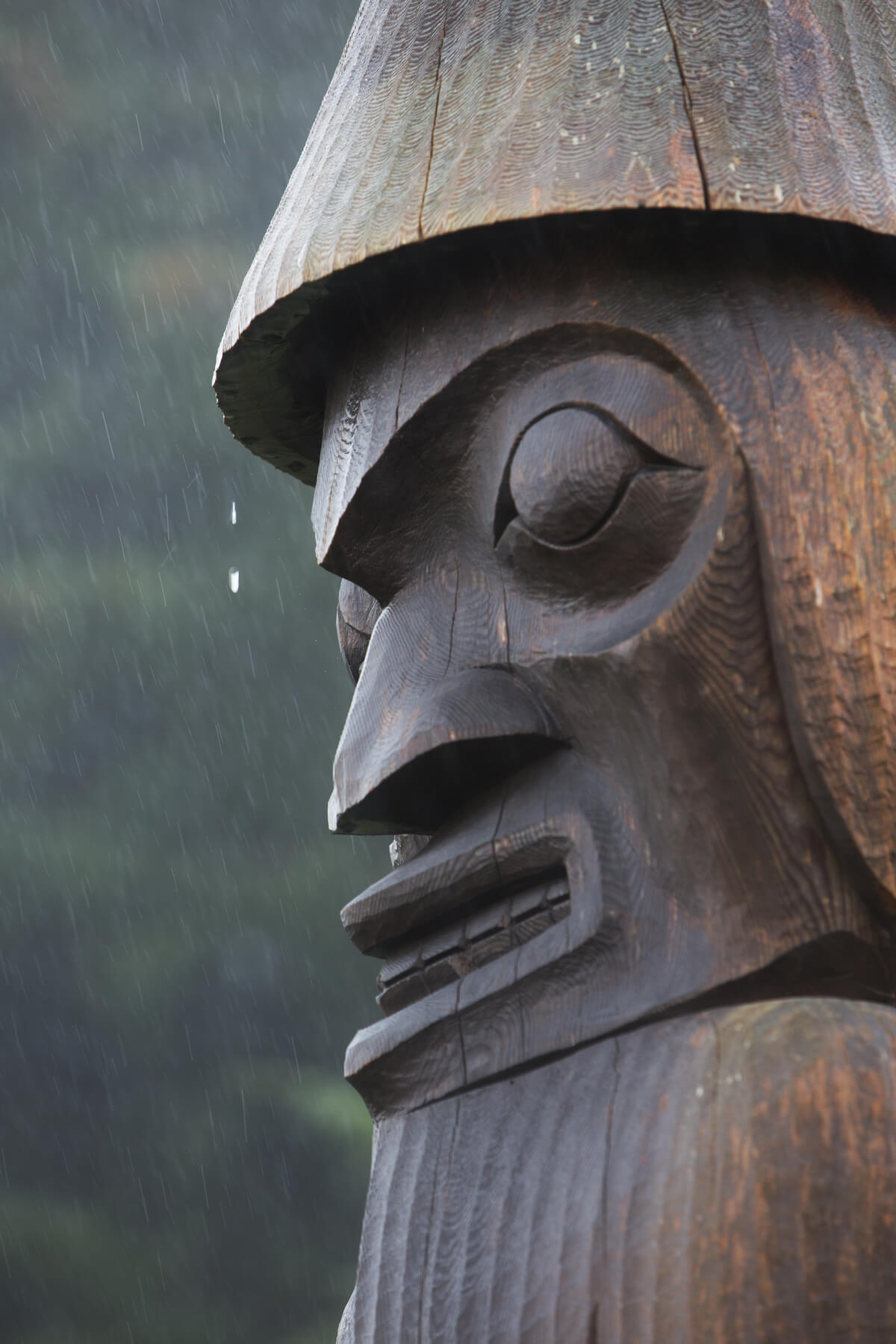 Close up of wooden carved totem pole in Yuquot, at the end/start of te Nootka Trail