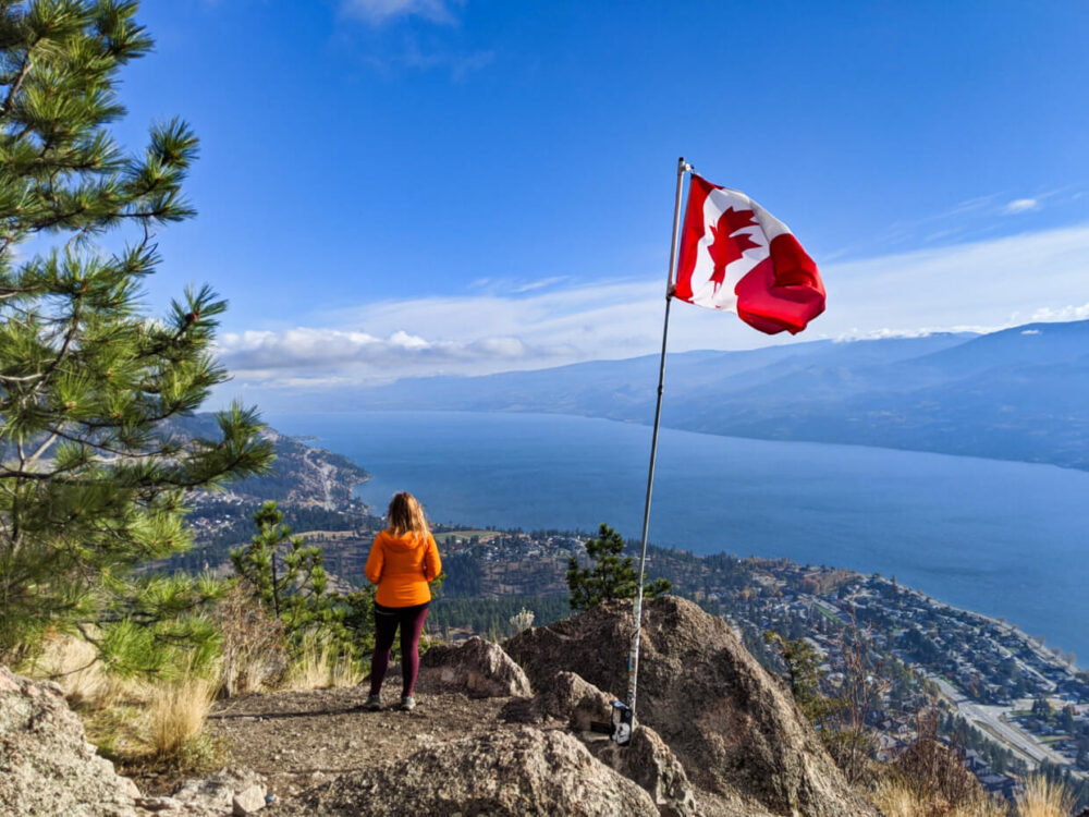 Gemma standing on the Pincushion Mountain summit looking at beautiful lake and lakeshore views on sunny day with Canadian flag flying adjacent