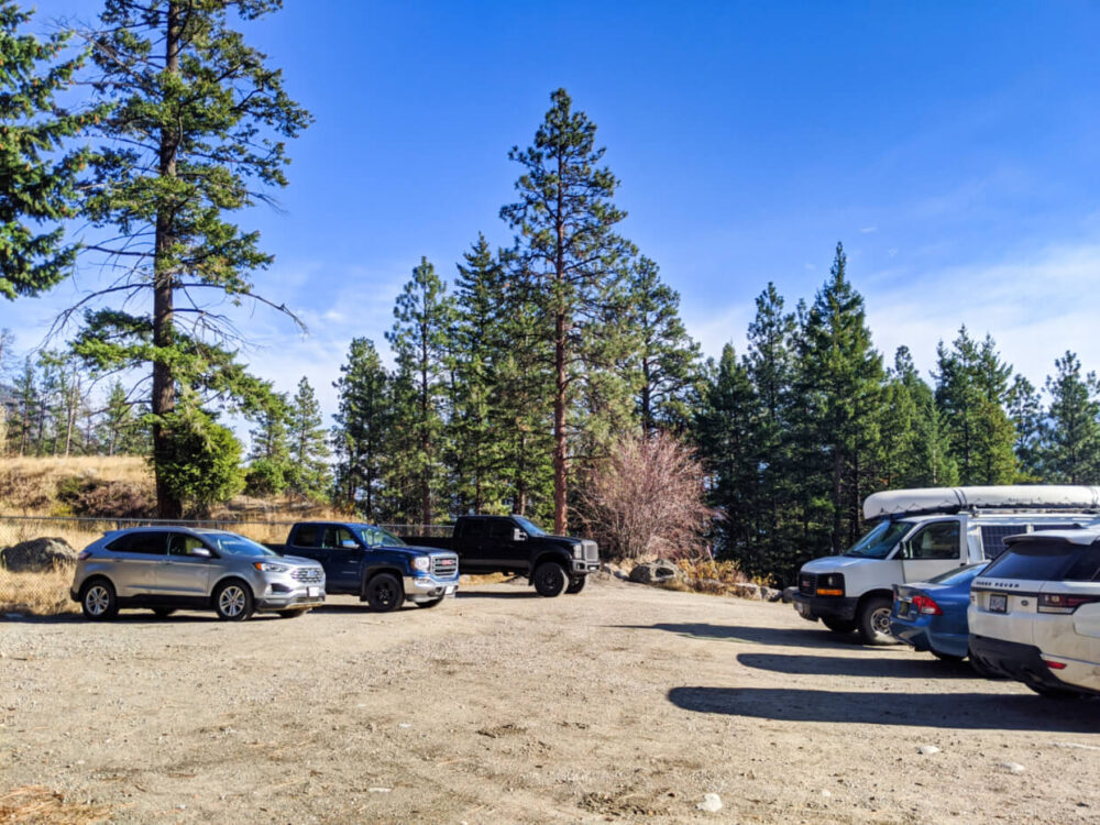 Pincushion Mountain parking lot with dirt surface, seven vehicles and background of pine trees