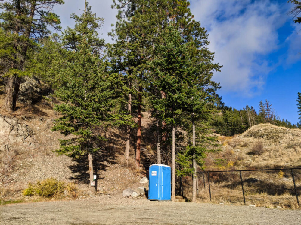 Looking across the Pincushion Mountain parking lot to blue porta potty standing next to trailhead with stairs visible behind