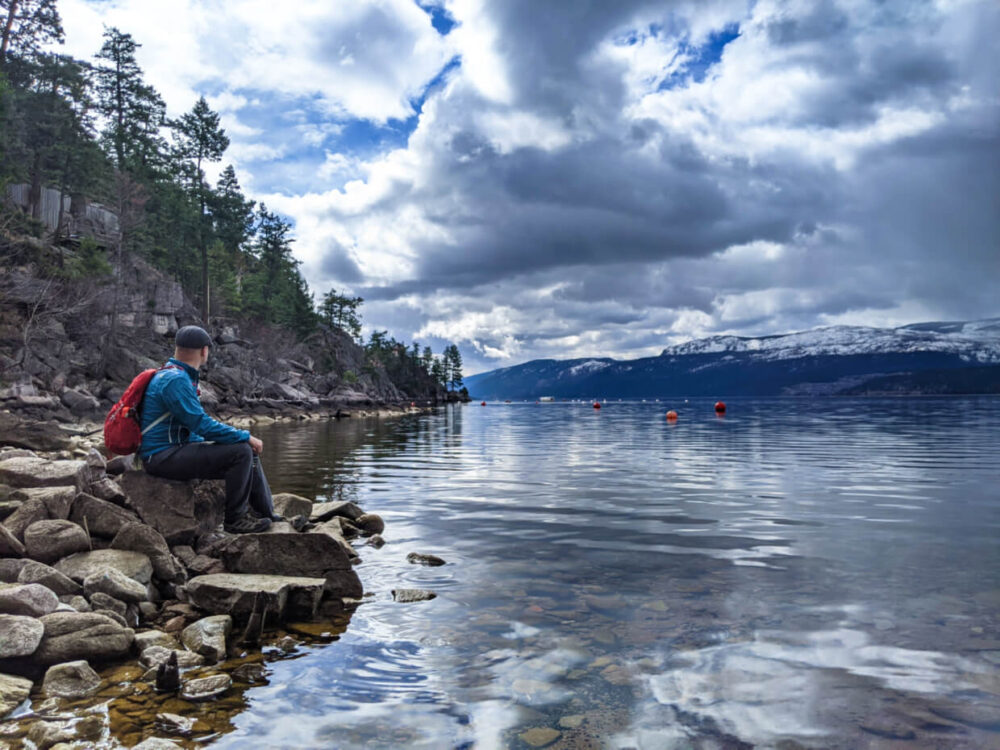 JR sits on a rock next to Okanagan Lake looking out towards snow capped mountains in the background. The lake surface is very calm.