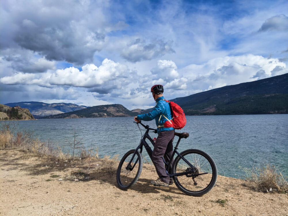 JR standing on electric assist cruiser bike next to Kalamalka Lake, looking towards hills in the distance