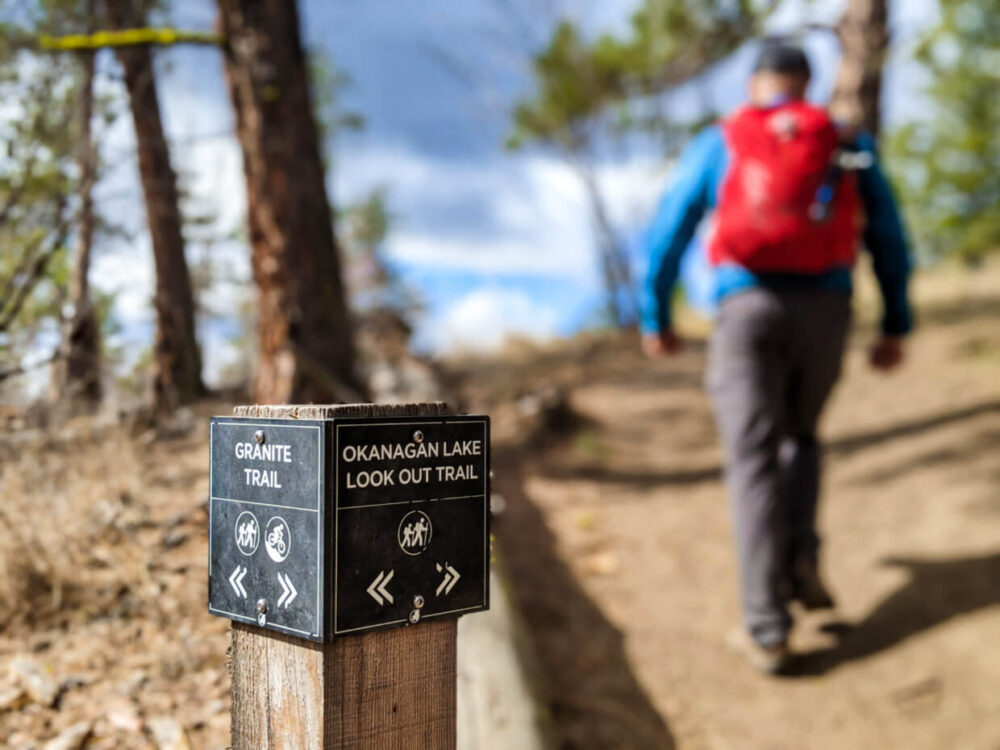 JR walks away from camera on right (out of focus) with Okanagan Lake Lookout Trail and Granite Trail sign in foreground