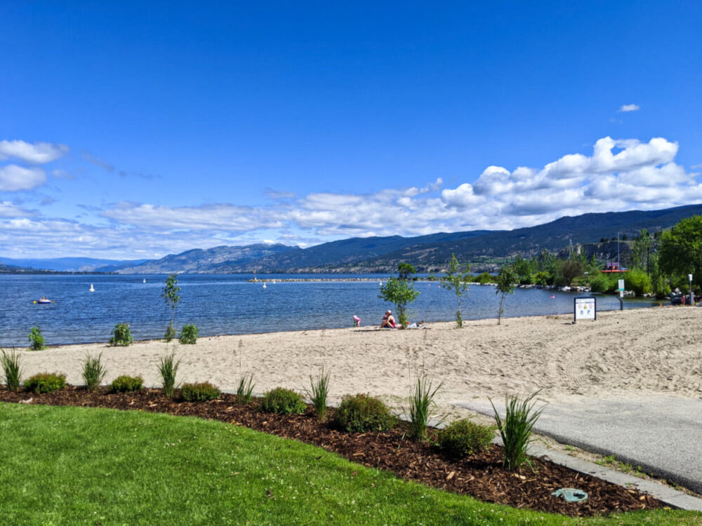 Looking across grassy patio area towards sandy beach next to lake, lined by hills