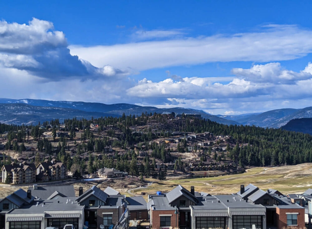 Trail photo looking over Predator Ridge houses towards forested ridge with more houses and Sparkling Hill Resort