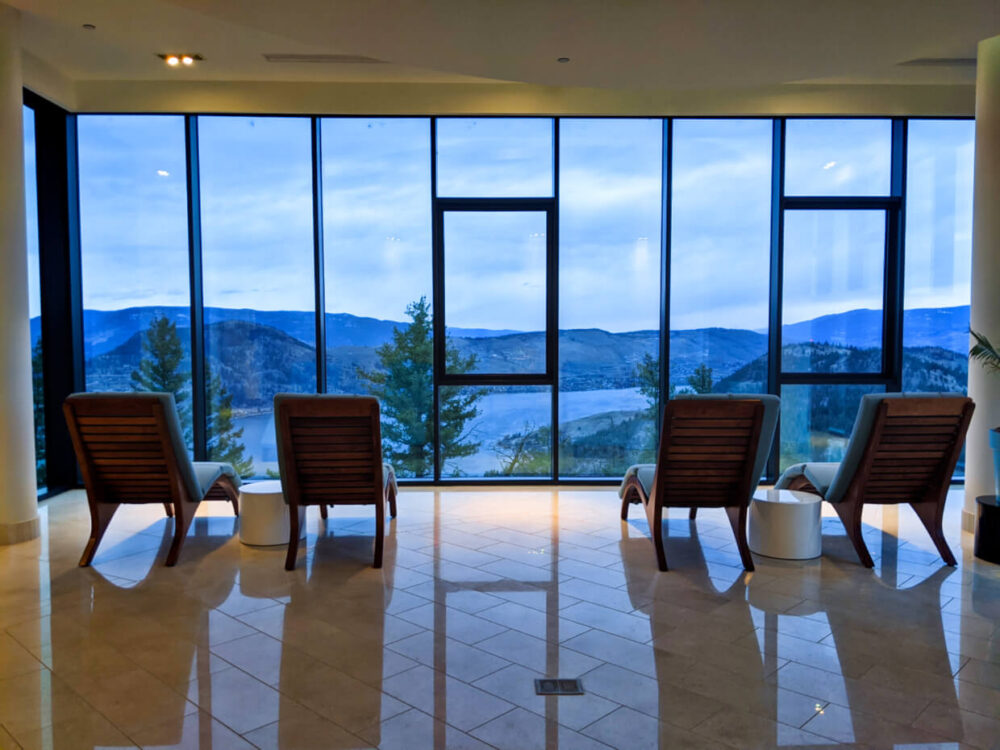 Four spa seats are lined up in front of floor to ceiling windows, looking out to Okanagan Valley scenery