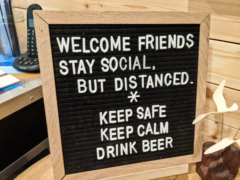 Wooden sign at Penticton restaurant with the phrasing 'Welcome Friends, Stay Social, but distanced. Keep Safe, Keep Calm, Drink Beer.'