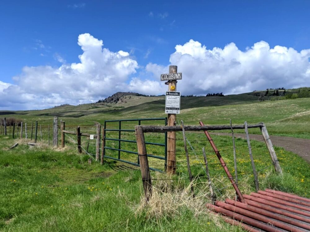 Side view of cattle gate in front of grasslands area, with trail signage visible
