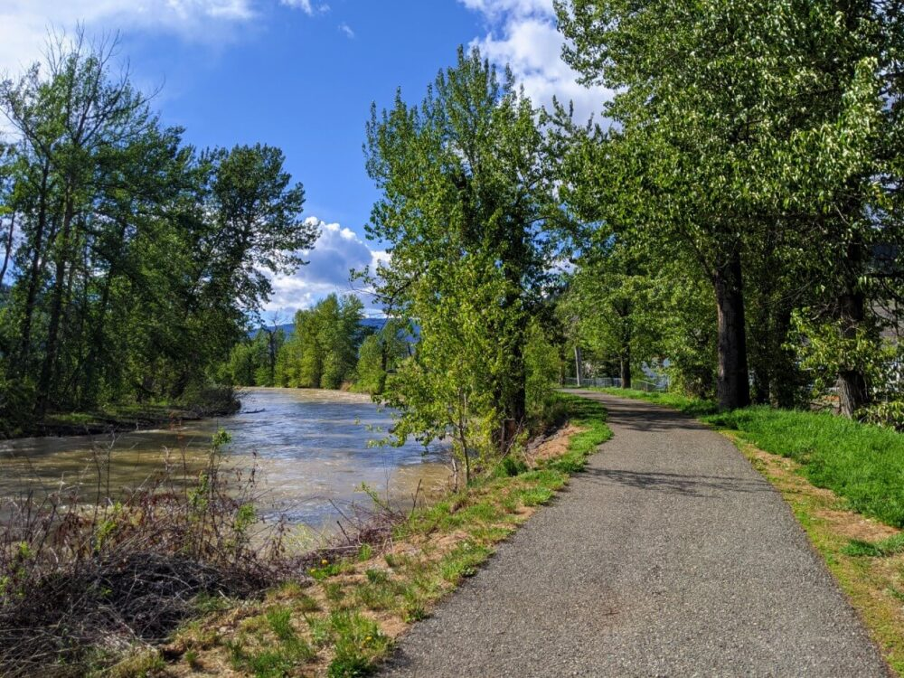 A paved trail (the Coldwater River Trail) runs alongside a rushing river, which is milky in colour. There are trees along the path