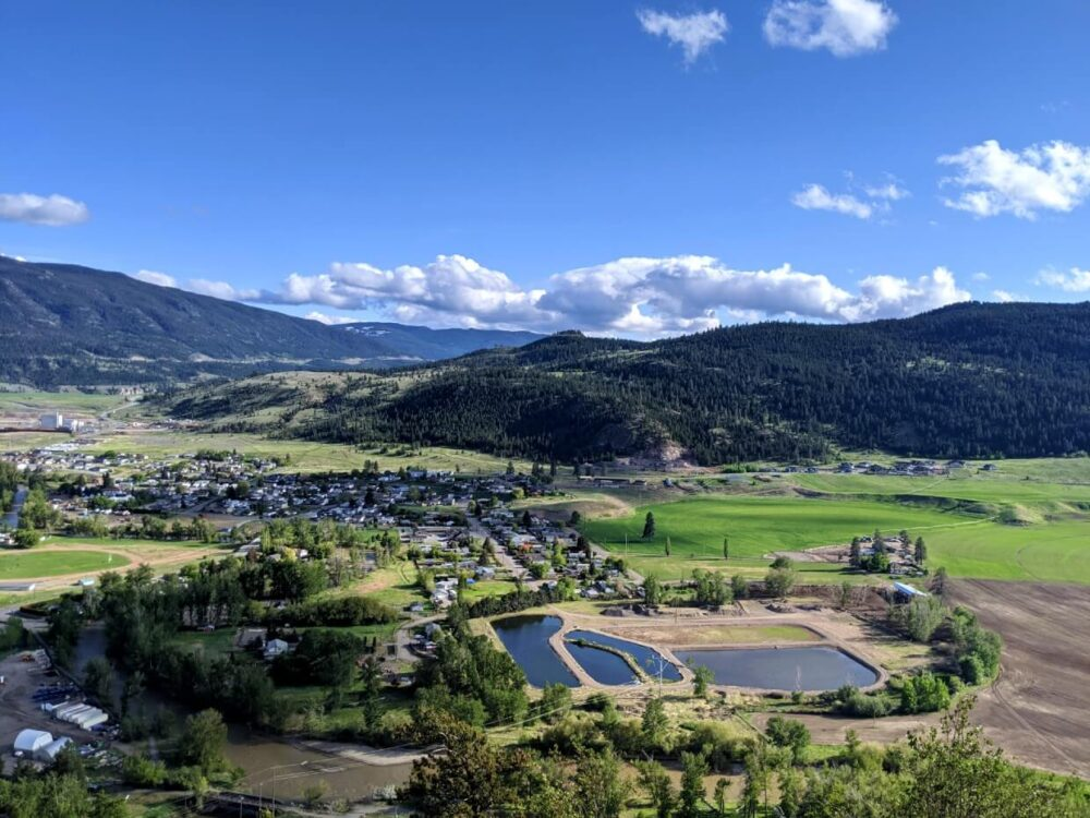 Elevated view looking down from flagpole viewpoint in Merritt, across housing areas to forested plateau and highway beyond