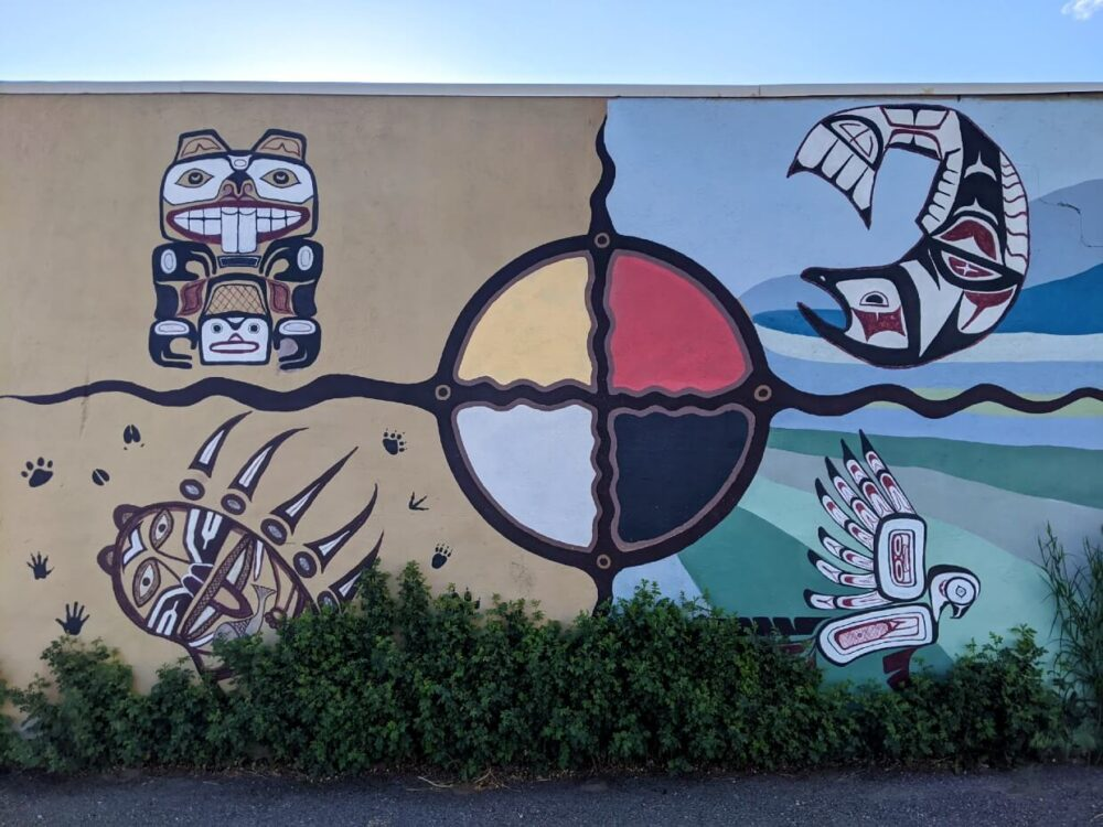 View of indigenous artwork in downtown Merritt - a wall divided into four with one animal in each corner (from top right: beaver, salmon, bird and bear paw)