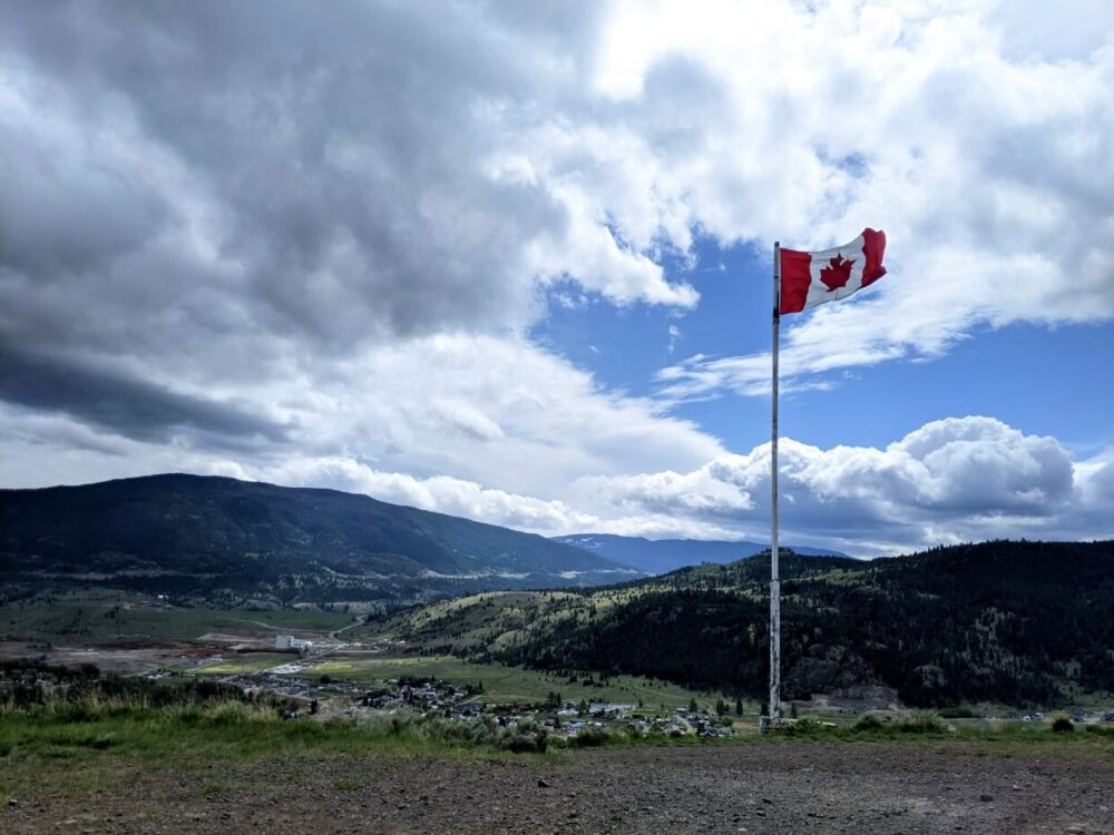 Looking across to Canadian flag flying on flagpole above the city of Merritt