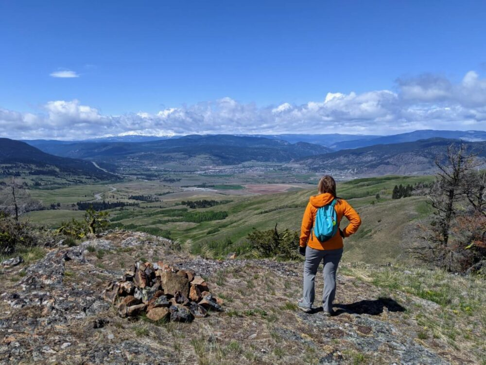 Gemma stands at the summit of Sugarloaf Mountain, looking out towards Merritt and the snow capped mountains behind
