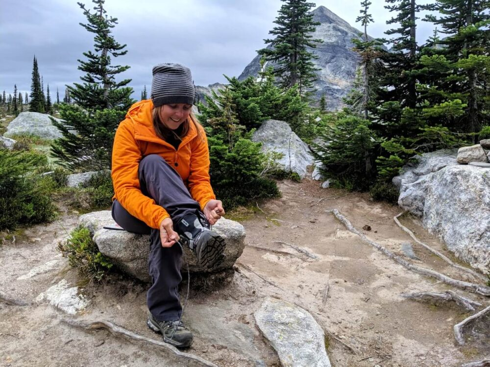 Gemma is sat on a rock tying up her boot shoe laces in alpine area while backpacking