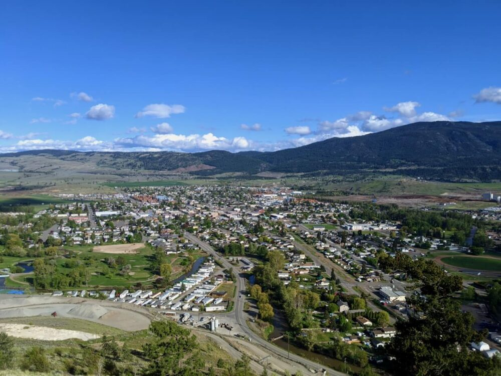 Elevated view looking down on the city of Merritt, with houses and highways leading away from camera, forested hills and mountains in background