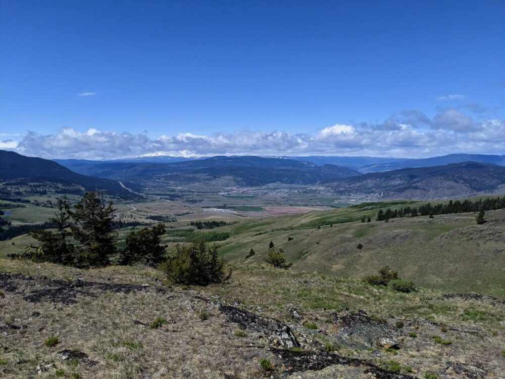 Elevated view looking down from mountain summit towards the city of Merritt, with rolling hills and snow capped mountains in background