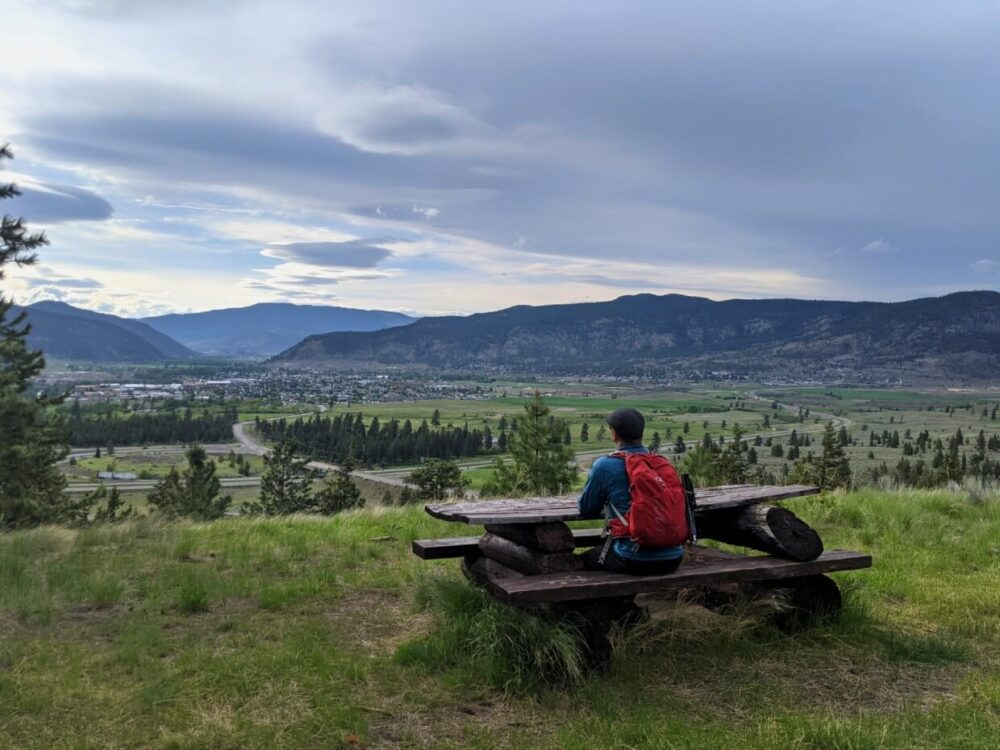 JR is sat with his back to camera, sat at a wooden picnic table looking out to views of Merritt and the Nicola Valley