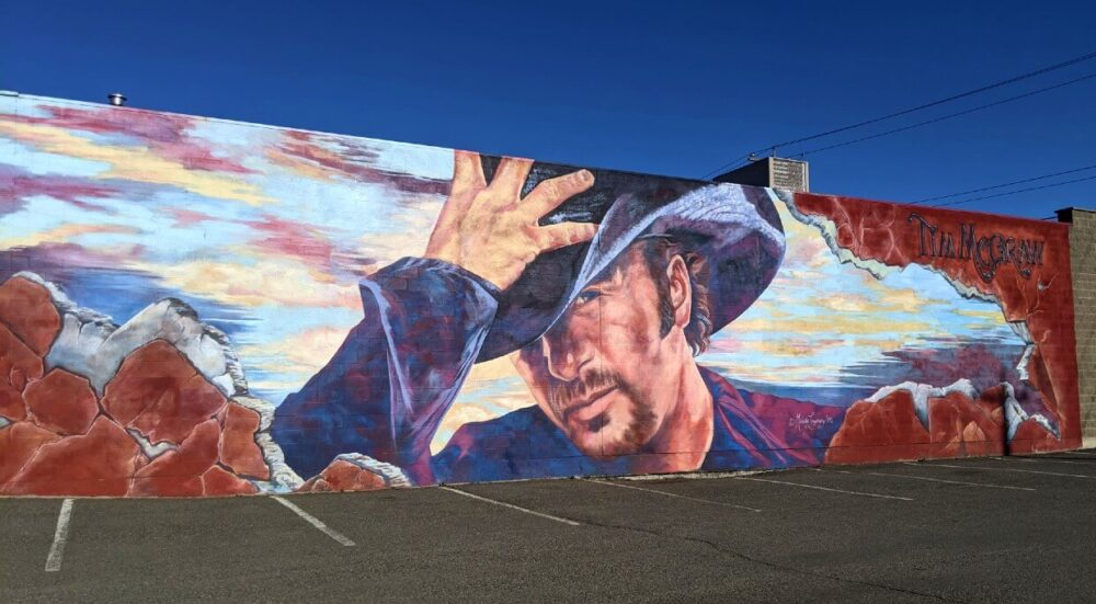 View of huge mural on side of building, depicting a bearded man (Tim McGraw) wearing cowboy hat with sunset-like background.