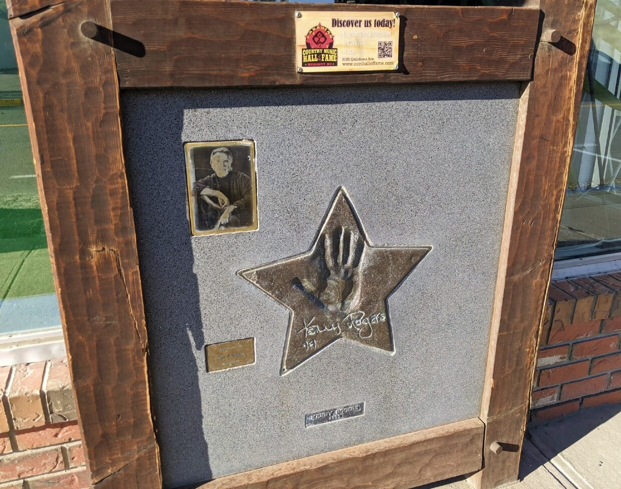 Close up of embossed gold star with Kenny Rogers hand print and signature on wooden plaque, with photograph of musician on left