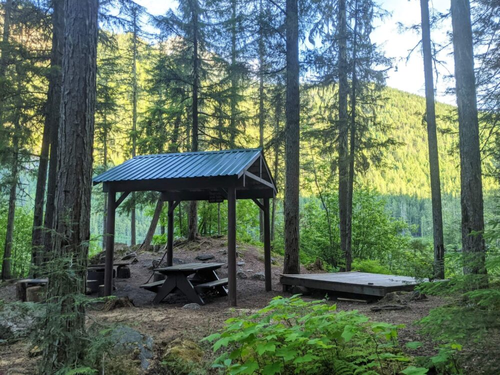 Distant view of wooden tent pad next to picnic table with shelter, with lake visible in the background