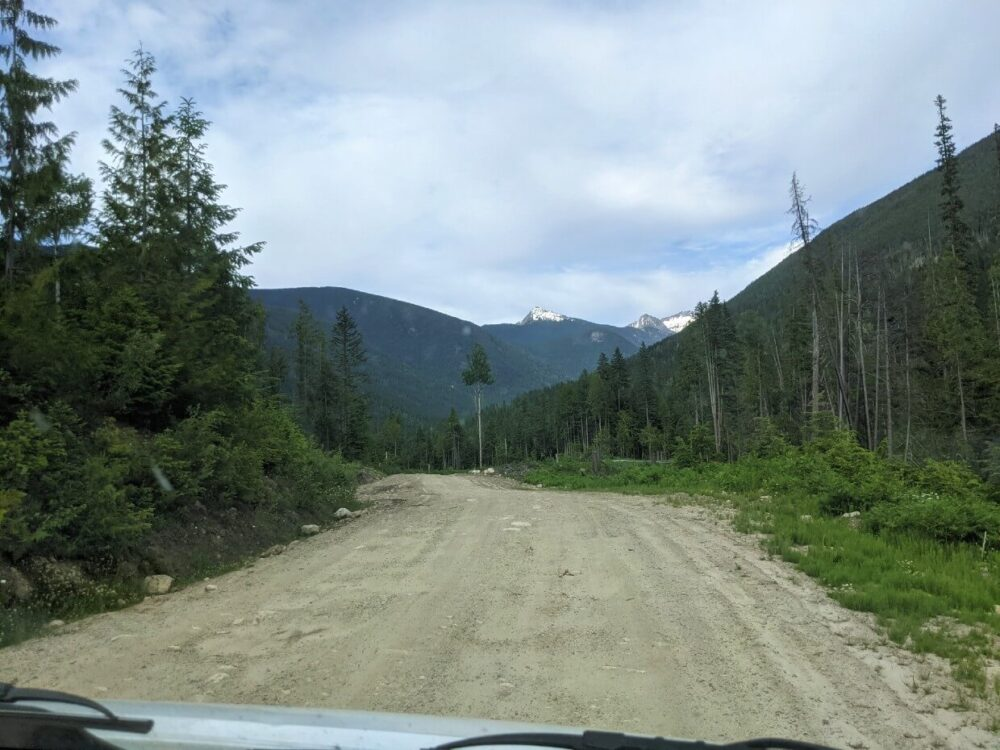 View through vehicle windscreen towards unpaved road, with mountains in background