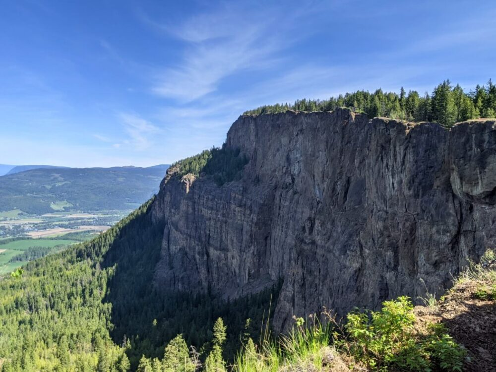 Side view of huge cliffs riding out of forest, with ridge visible on right