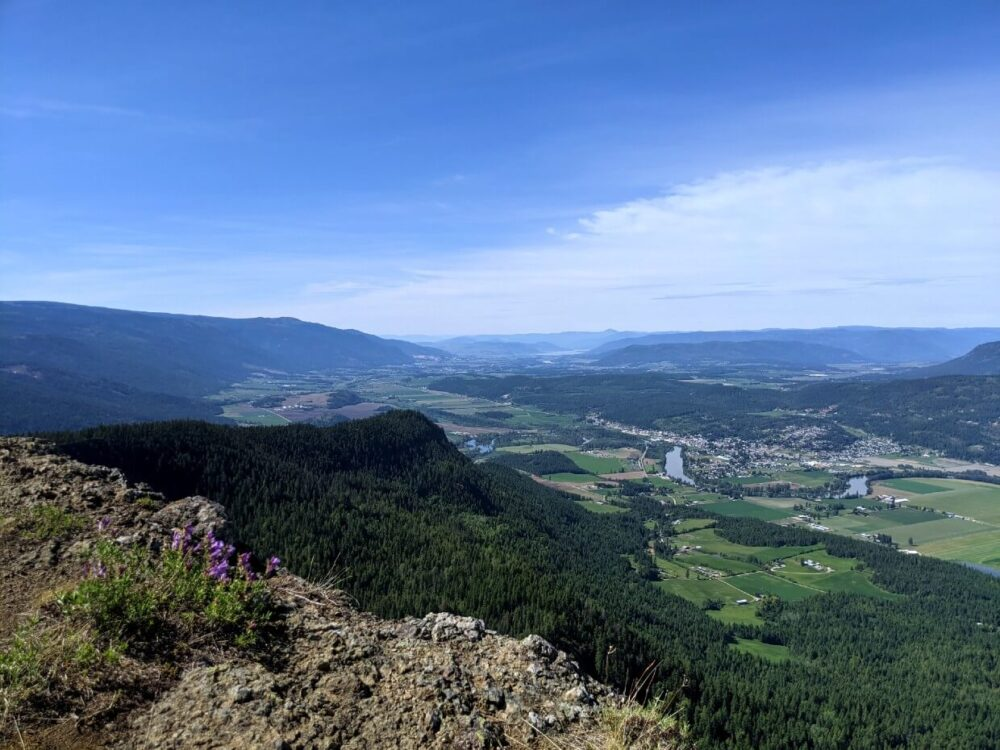 Looking out over rocky ridge towards spectacular views of farmland and rolling hills below, as seen from the Enderby Cliffs hike