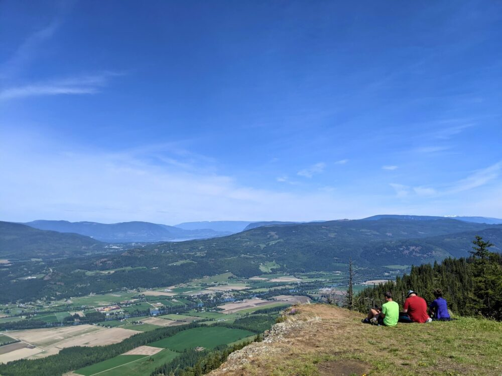 Three hikers in brightly coloured tops sit on the grass in front of gorgeous farmland views on the Enderby Cliffs Trail
