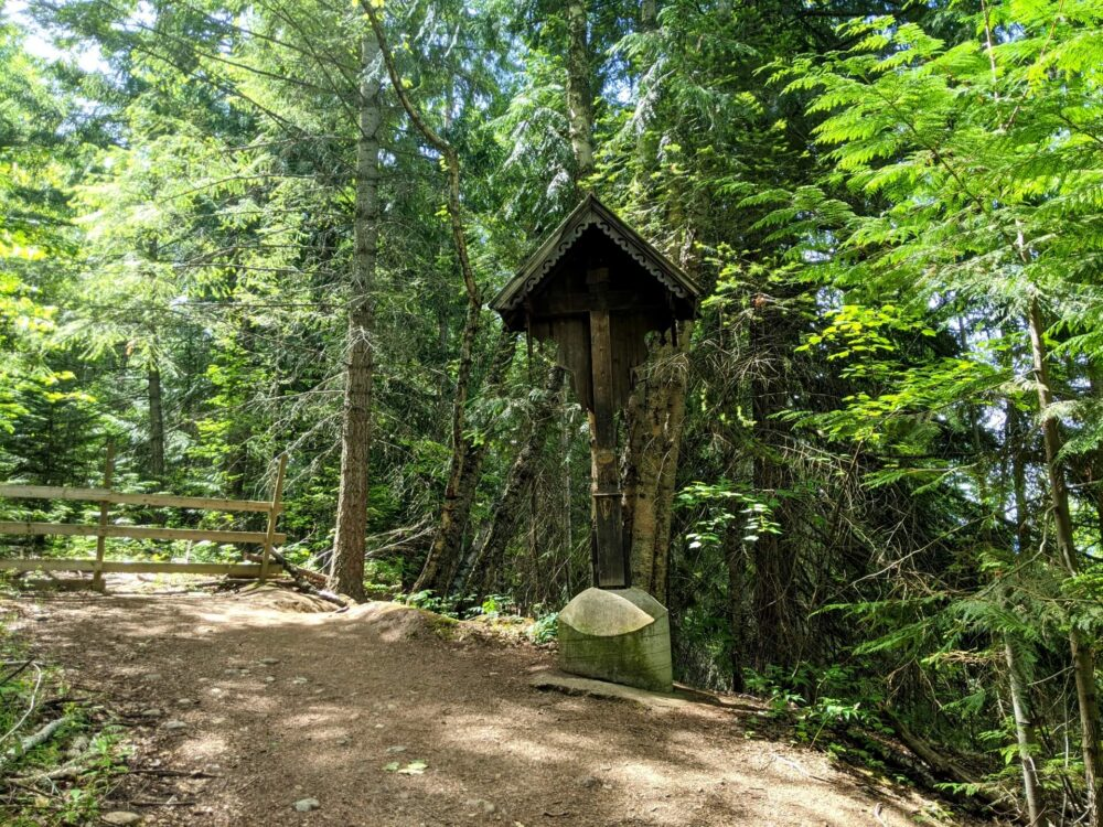 Side view of dirt hiking trail in forest with wooden shrine, with cover over cross