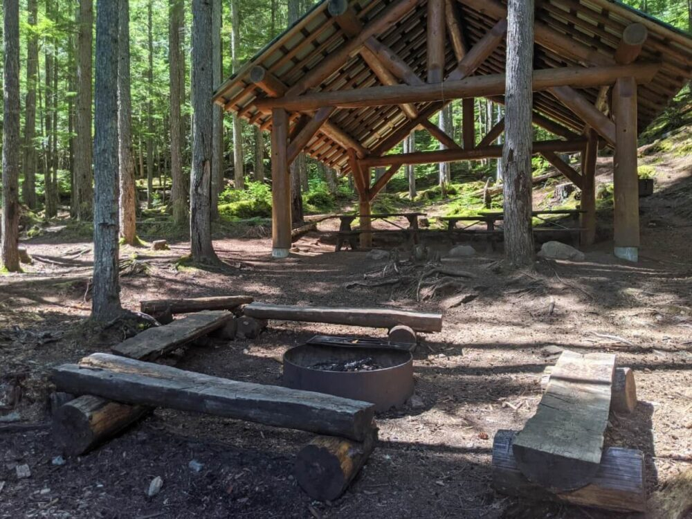 Looking across communal fit pit area with benches to large shelter with three picnic tables underneath in Spectrum Lake group campground