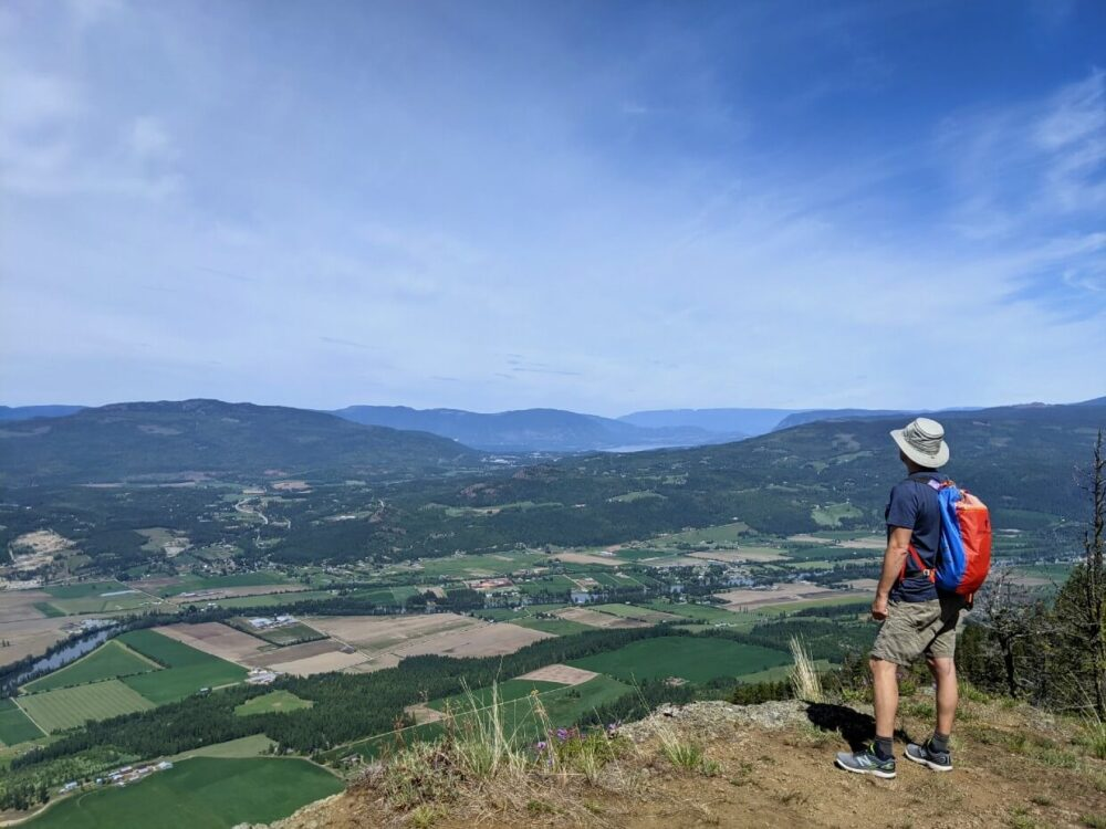 JR stands on the edge of Enderby Cliffs, looking out at views of rolling farmland far below
