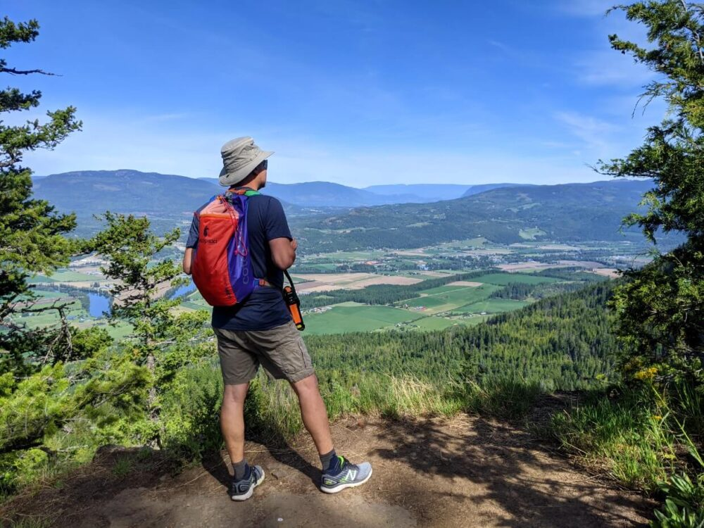 JR stands on the edge of Enderby Cliffs, looking out at views of rolling farmland