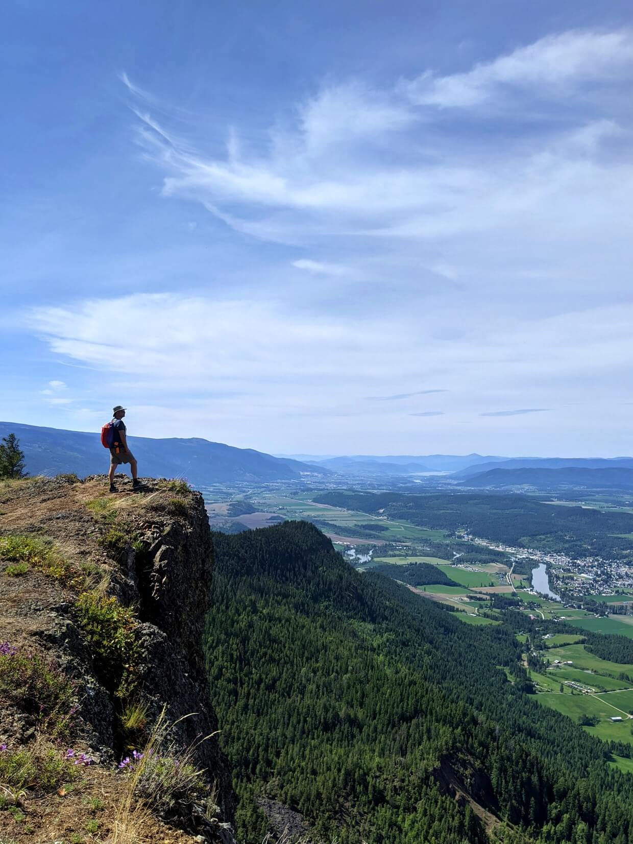 JR stands on the edge of a ridge on the Enderby Cliffs Trail, looking out at views of rolling farmland and  the forest below plus a highway, the city of Vernon and Okanagan Lake