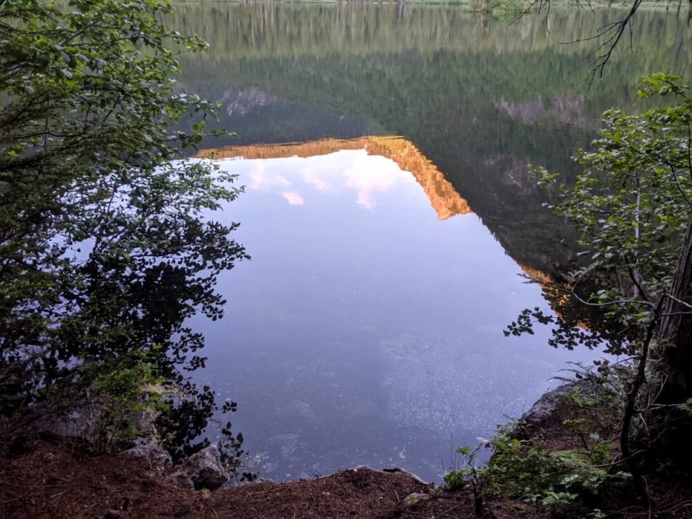 Sunset reflections on Spectrum Lake, with mountain peak lit up in red visible on lake surface