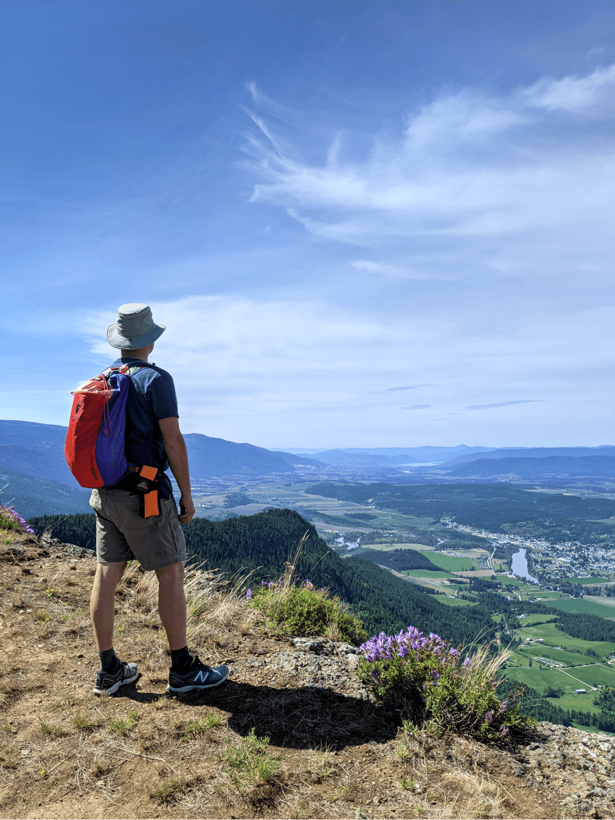 JR stands on the edge of Enderby Cliffs, looking out at views of rolling farmland, a highway and in the distance, the city of Vernon and Okanagan Lake