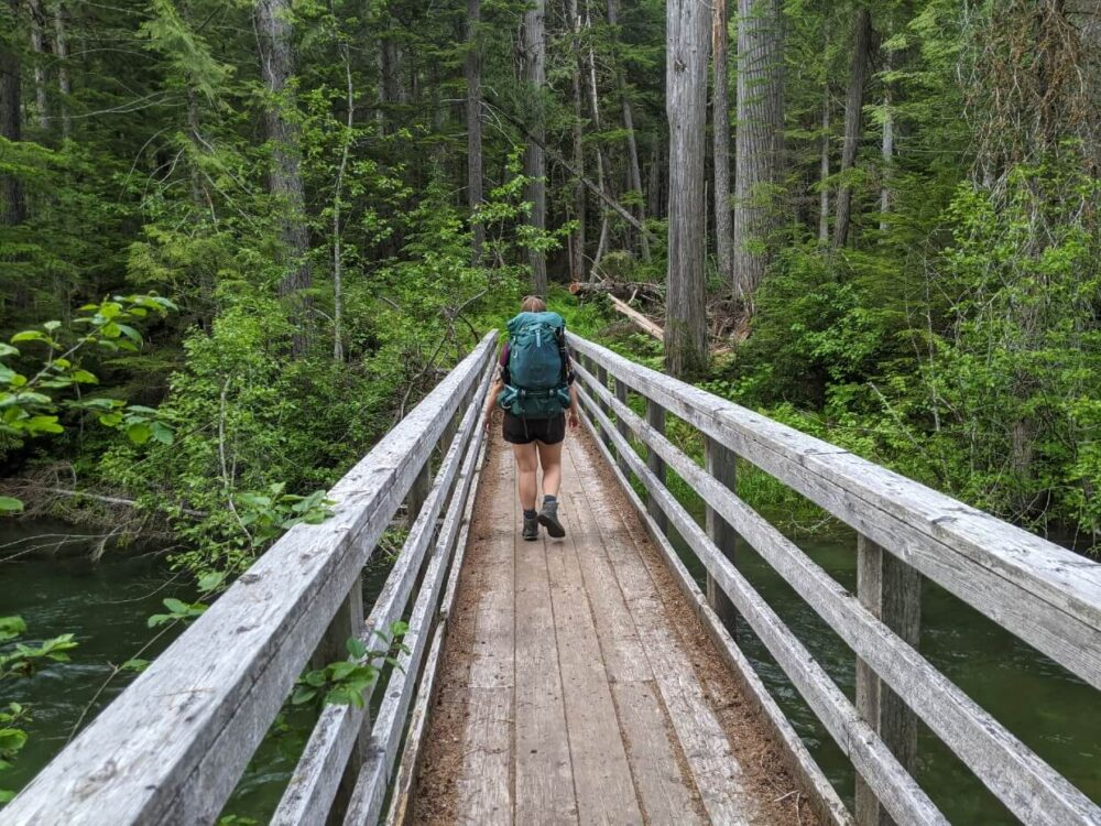 Back view of Gemma hiking away from camera on wooden bridge over river, carrying large turquoise backpack