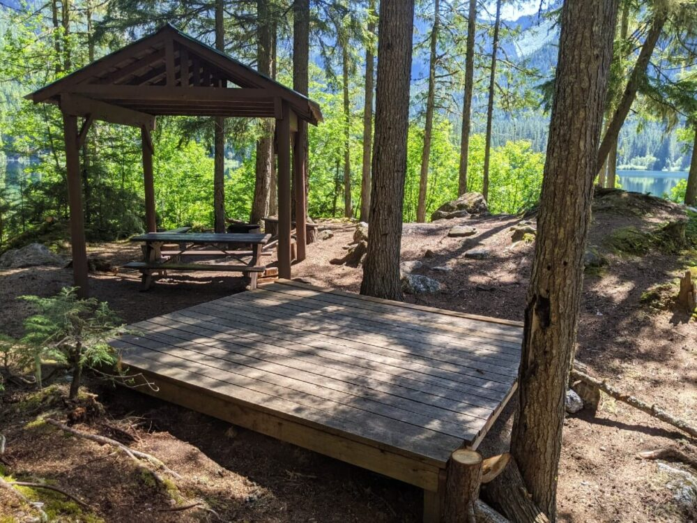 Raised wooden tent pad in front of picnic table with shelter, with lake visible in the background