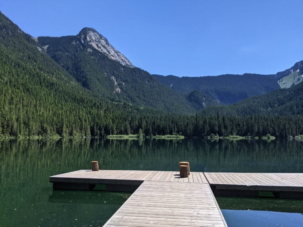 Looking across a T shaped dock on a lake to the mountain peak beyond. The lake surface is very calm
