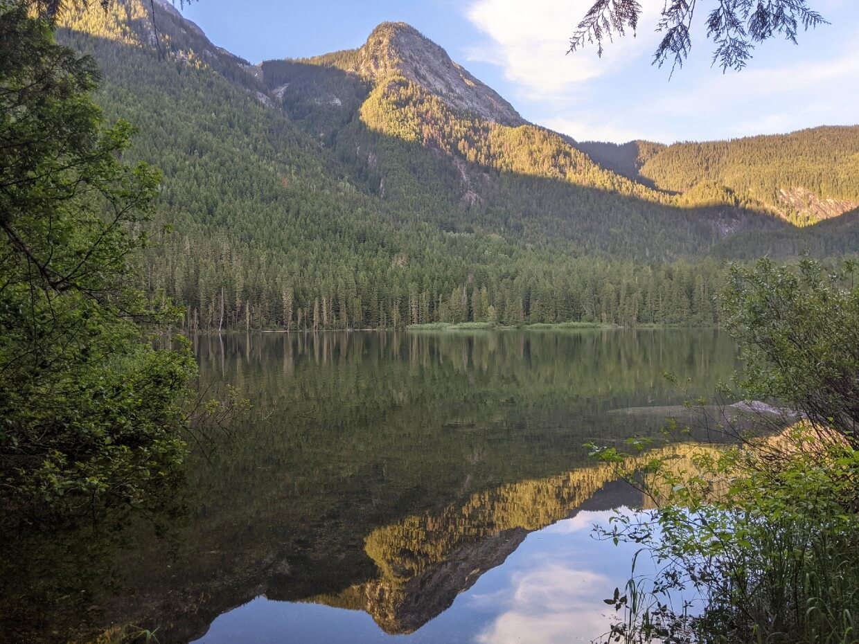 Spectrum Lake reflections, as seen through the trees. There is a mountain peak on the left, reflected onto the mirror like surface of the lake