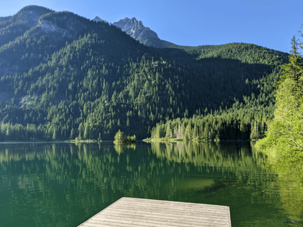 Looking past the end of the wooden dock at Spectrum Lake to calm lake surface with mountain peak in the background