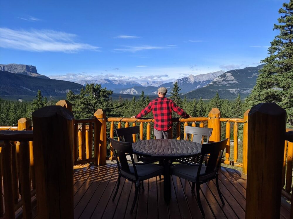 Back view of JR standing in front of table for four on outside patio at the Overlander, with views of mountains behind