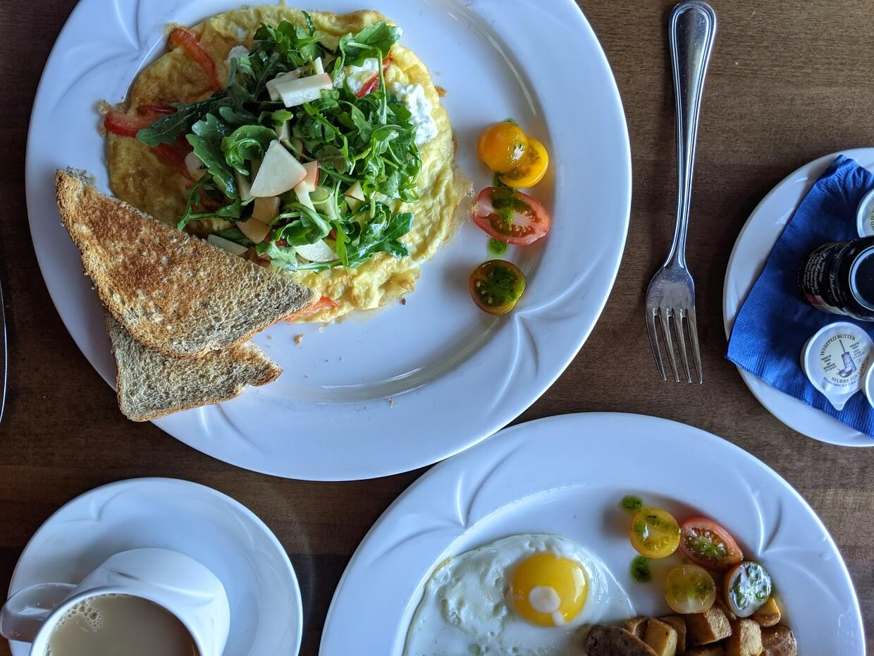 Overhead view of breakfast at Stone Peak Restaurant, with a cup of tea, a white plate with omlette and toast, and another plate with eggs and potatoes
