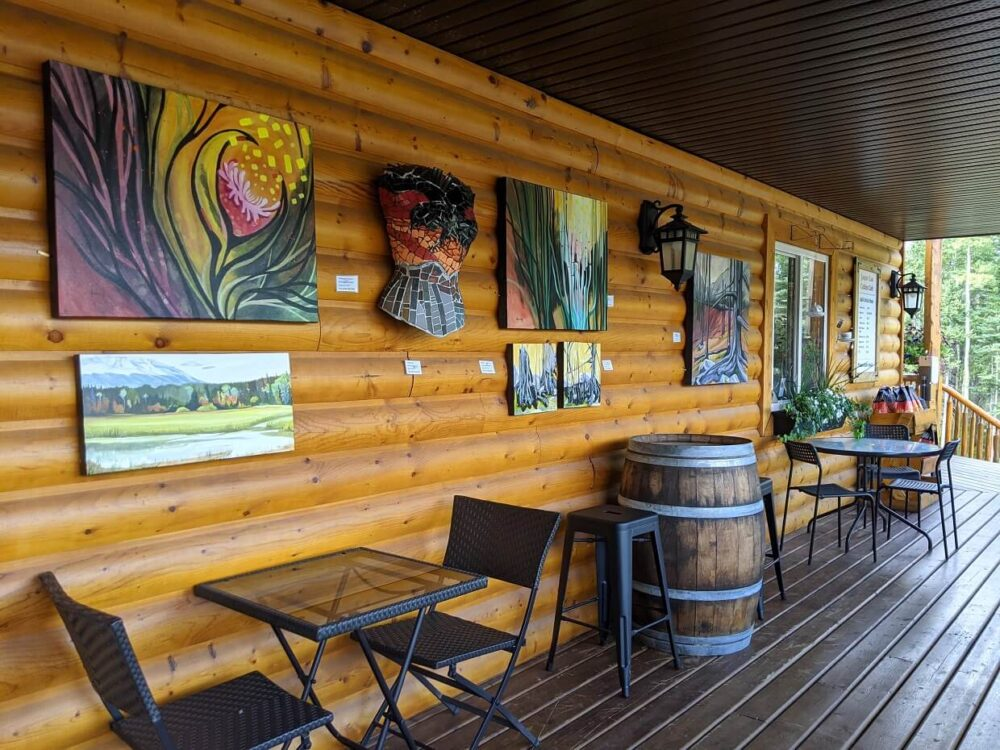 Jasper East Cabins Gallery - wooden patio with tables and chairs nxt to individual pieces of art dispalyed on wooden cabin wall
