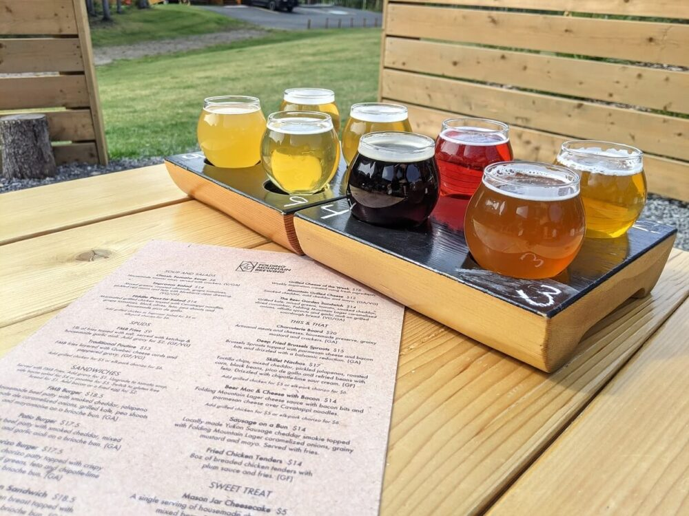 Side view of two flights of beer, with eight glasses of differently coloured beer, on wooden picnic table with Folding Mountain Brewery menu in front