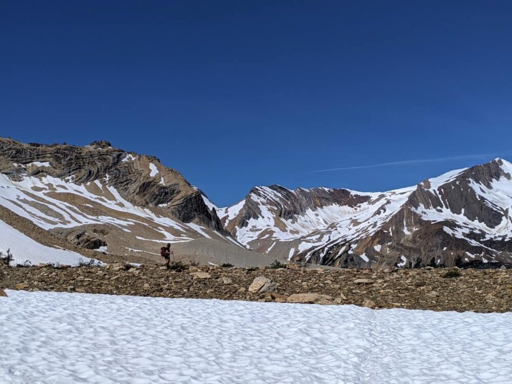 Looking across a snow patch towards Gemma, who is hiking on a rocky area in front of snow capped mountains