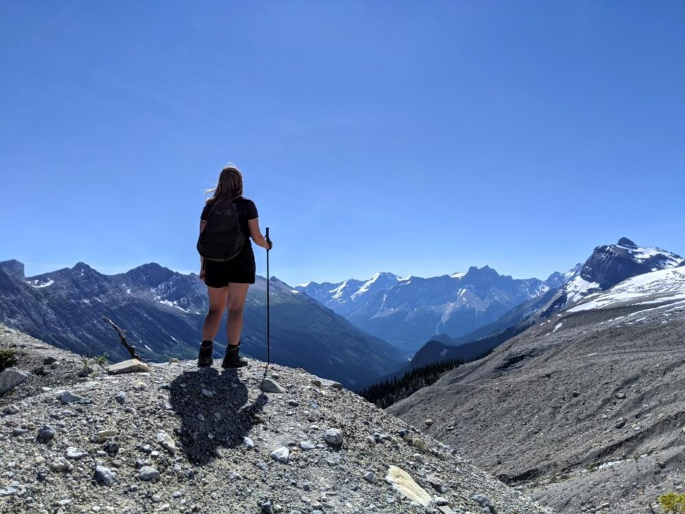 Back view of Gemma standing on top of rocky viewpoint, looking out to endless mountain views