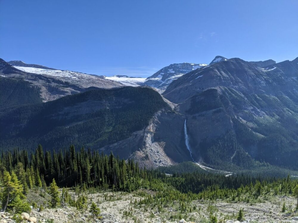 Looking own towards a glacier field on the Iceline Trail, with Takakkaw Falls cascading from the rock into the forested valley below