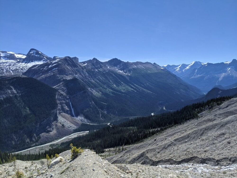 Looking across glacier moraine towards mountains and glaciers on other side of valley, with large cascading waterfall (Takakkaw Falls) on left hand side