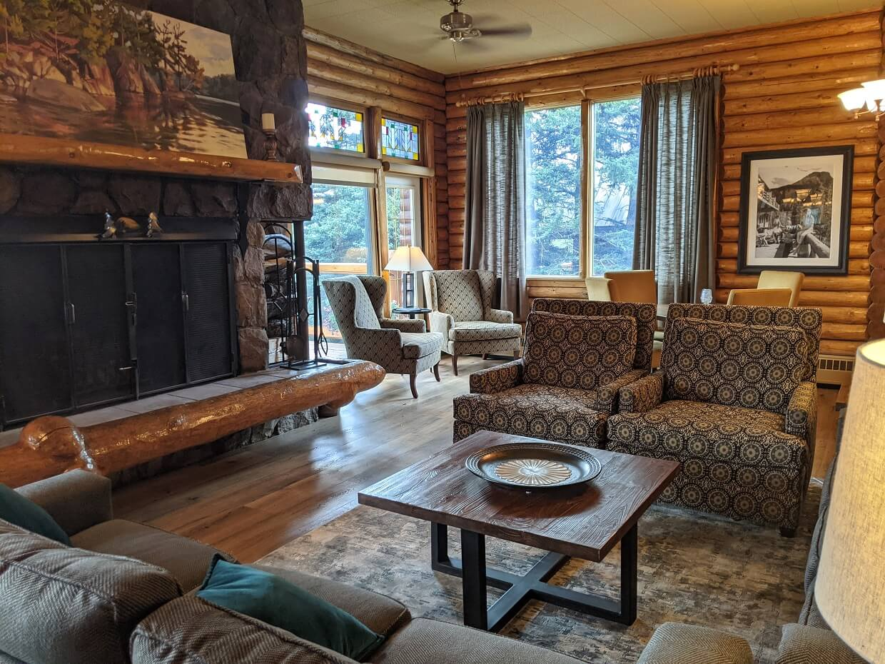Cosy lodge are with couches and comfortable seating in front of fire hearth