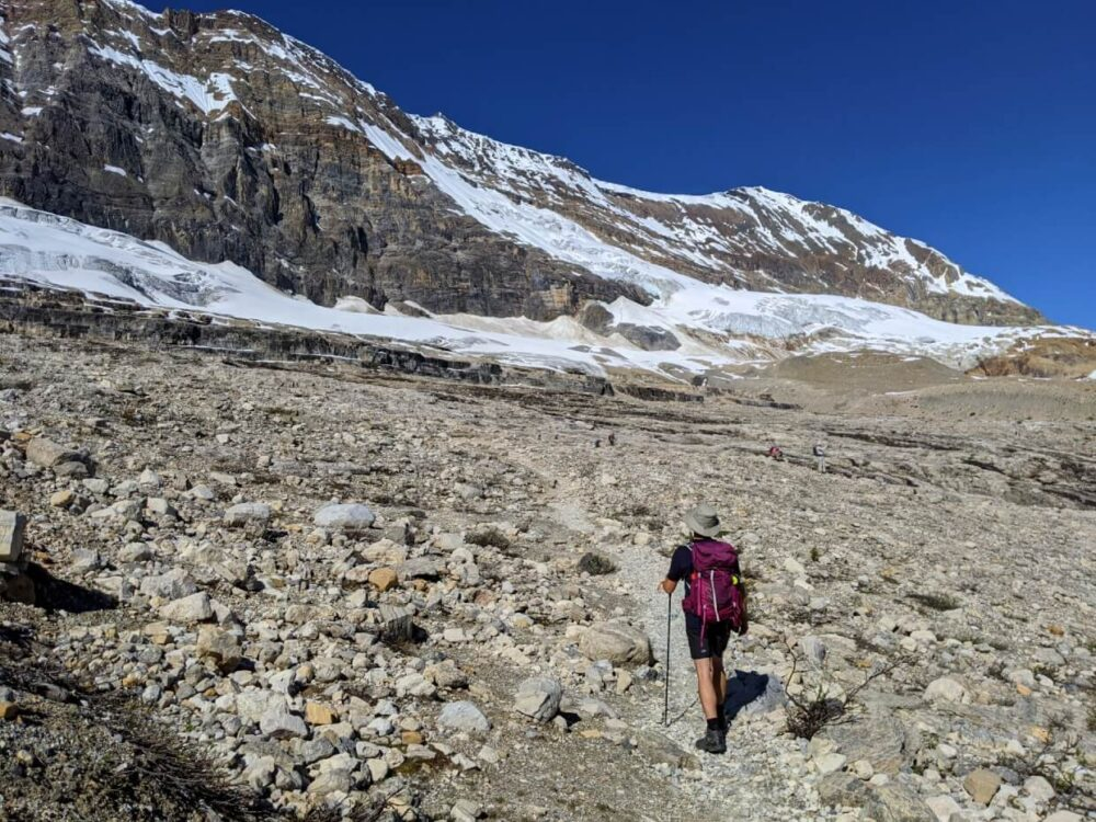 JR has his back to camera and is hiking on the Iceline Trail through rocky landscape towards a glacier, backed by a steep cliff